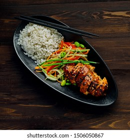 Chicken with savory and sweet teriyaki sauce, cucumber, cabbage, ginger and carrot salad, rice, sesame and edamame in a black pottery dish. Top view, directly above.