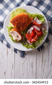 Chicken schnitzel cordon bleu and a salad on a plate on a table. vertical top view