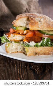 Chicken Schnitzel on a roll (wooden background)