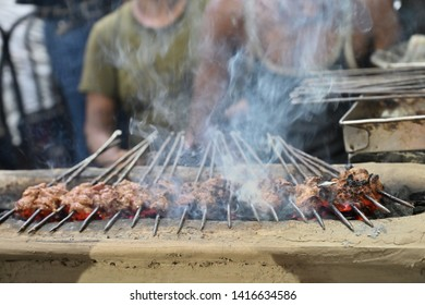 Chicken seekh kababs are being grilled with heat in barbeque with metal skewers,at evening for sale as street food in Kolkata, India. India is famous for spicy Indian non vegetarian street foods.
