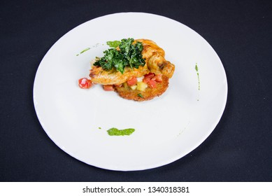 Chicken served with potato pancake some vegetables decorated with pea mash