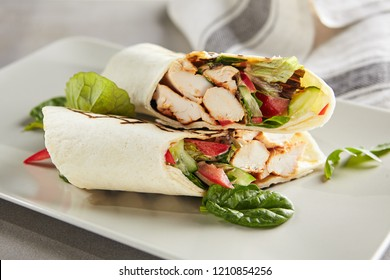 Chicken Shaverma or Doner Kebab with Vegetables on a White Plate Close Up. Rolls of Wheat Tortillas Stuffed with Turkey Fillet Cucumber, Tomato and Greens
