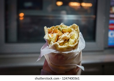 Chicken shawarma with fries and salad dressings wrapped in flat bread and paper held in hand after a few bites.