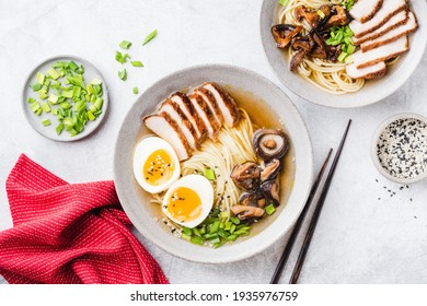 Chicken shiitake ramen noodle soup bowl on a grey concrete background, top view. Asian cuisine food, noodle soup with chicken, shiitake, egg and green onion known as Ramen