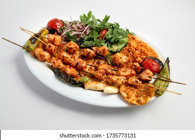 Chicken shish kebab on a serving plate. Served with salad and rice