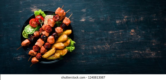 Chicken shish kebab with potatoes and vegetables on a black background. Meat. Top view. Free copy space.