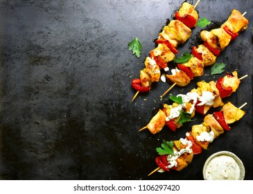 Chicken skewer kebab with bell pepper and yogurt sauce on a black metal, slate or stone background.Top view with copy space.