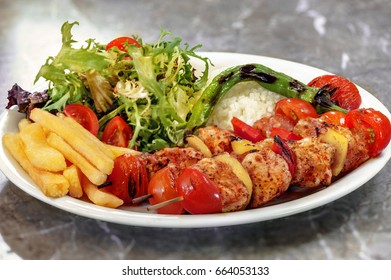 Chicken skewers, french fries and rice with leaf vegetable.