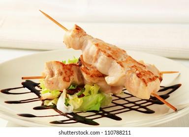 Chicken skewers garnished with balsamic vinegar
