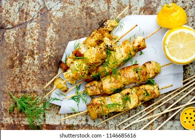 Chicken skewers with pineapple slices with dill and lemon on white paper napkin on an old metal background top view