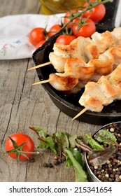 Chicken skewers with vegetables on wooden table