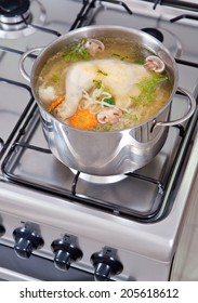 chicken soup being cooked on a gas stove