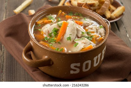 Chicken soup in a bowl with crackers.