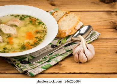 Chicken soup with a bread and garlic on the wooden background.
