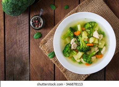 Chicken soup with broccoli, green peas, carrots and celery in a white bowl on a wooden background in rustic style. Top view