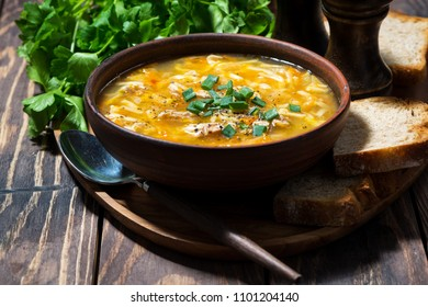 chicken soup with egg noodles in a bowl on wooden background, horizontal