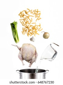 Chicken soup ingredients falling into stock pot