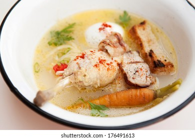 Chicken soup with noodles, crouton, egg and vegetables close up a