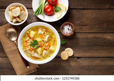 Chicken soup with noodles and vegetables in white bowl on  wooden background