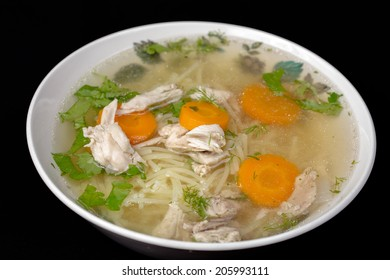 Chicken soup with vegetables isolated on black background.
