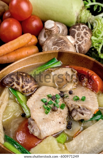 chicken soup with vegetables on table