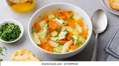 Hühnersuppe mit Gemüse in weißer Schüssel. grauer Hintergrund. Nahaufnahme.