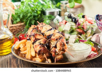 Chicken Souvlaki with french fries and tzatziki sauce. Greek dish on a plate