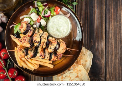 Chicken Souvlaki with french fries and tzatziki sauce. Greek dish on a plate. Top view