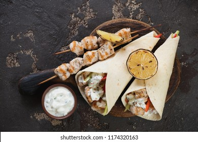 Chicken souvlaki with tzatziki sauce on a wooden serving board, view from above on a brown stone background, horizontal shot