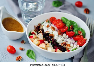 Chicken spinach apple tomato goat cheese salad. toning. selective focus