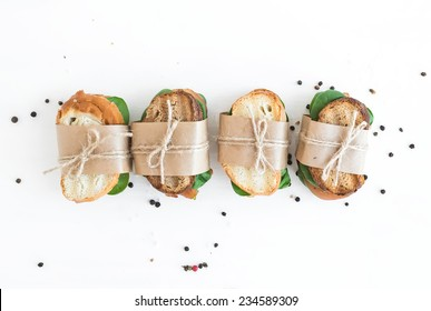 Chicken and spinach sandwiches wrapped in craft paper over a white wooden background with a copy space