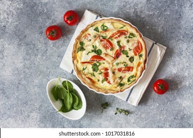 Chicken, spinach and tomatoes pie( quiche) on a blue stone background. Top view