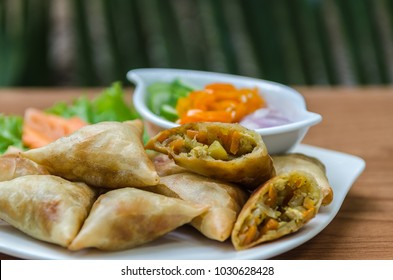 Chicken Spring Roll, Curry, snack.(Samosa), On a white plate on a wooden table, a tree background blurred.