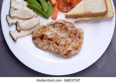 Chicken steak in white dish top view