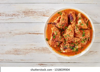 Chicken stewed in creamy spicy Coconut gravy, kuku paka, served on a white plate on an old wooden table, view from above, close-up, copy space