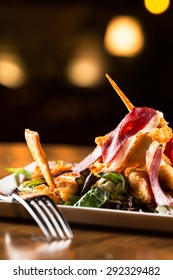 Chicken sticks with duck ham and salad.