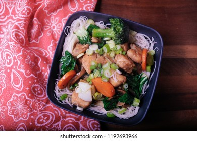 chicken stir fry with rice noodles and fresh vegetables