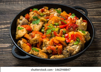 Chicken Stir fry with vegetables in the black iron plate on dark wooden table.