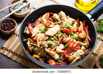 Chicken stir fry with   vegetables and sesame in the pan. Traditional asian food.