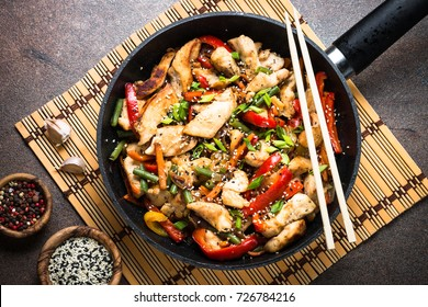 Chicken stir fry with   vegetables soy sause and sesame in the wok. Traditional asian food. Top view on rusty stone table.