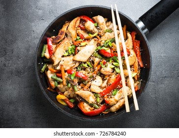 Chicken stir fry with   vegetables soy sause and sesame in the wok. Traditional chinese food. Top view on black.