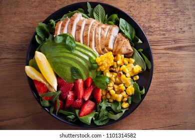 Chicken with strawberry, avocado, arugula, basil, mint and sweet corn salad. Balanced diet food bowl. overhead, horizontal