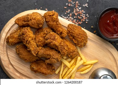 Chicken strips, french fries, and ketchup on a wooden tray. Fast food concept.