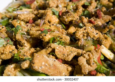 Chicken strips fried in batter with sesame seeds with coriander garnish.
