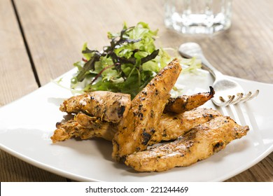 Chicken strips, on a white square plate with a side salad