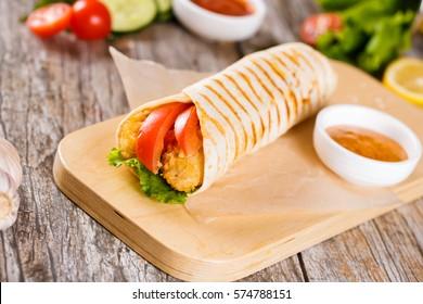 Chicken strips in Tortilla wrap on wood background.