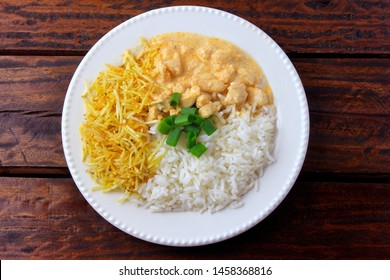 Chicken stroganoff, is a dish originating from Russian cuisine that in Brazil is composed of sour cream with tomato extract, rice and potato chips, on rustic wooden table. Top view