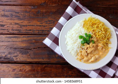 Chicken stroganoff, is a dish originating from Russian cuisine that in Brazil is composed of sour cream with tomato extract, rice and potato chips, on rustic wooden table. Top view.