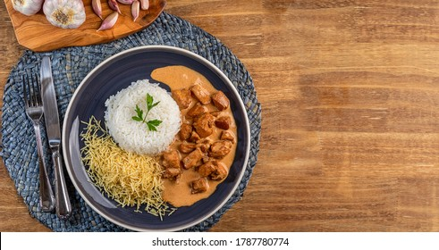 Chicken stroganoff with rice and french fries on a plate, over rustic wooden table. Top view. Space for text.