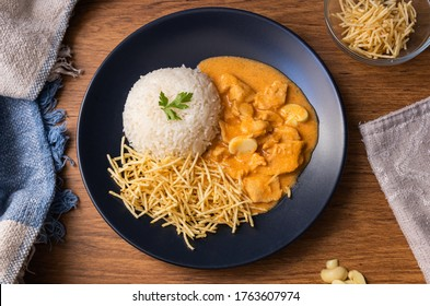 Chicken strogonoff with rice and french fries (potato sticks) on dish. Chicken stroganoff, is a dish originating from Russian cuisine.